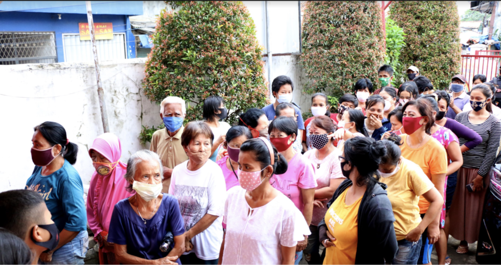 The families of GRP employees waiting in line to receive groceries and essential food